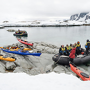 Kayaks and inflatable zodiacs pulled ashore at a landing point at Petermann Island on the Antarctic Peninsula.