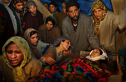 BEERU, INDIA, FEB. 27, 2004: Relatives mourn the death of Samreena Iqbal, 18,  who was killed ina an attack on Kashmir 's Chief Minister Mufti Mohammad Syed in Beeru,  25 miles west of Srinagar, February 27, 2004. The chief minister of Jammu and Kashmir escaped after two grenades were thrown.A spokesman of Jamiat-ul-Mujahideen, a hardline Kashmiri group, called newspaper offices in Srinagar to say they had carried out the attack.  Guerrilla violence in Kashmir has continued unabated despite peace moves by India and Pakistan, who both claim the Himalayan region.