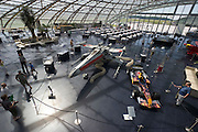 """Hangar-7; the spectacular home of the Flying Bulls (""""Red Bull"""" owner Didi Mateschitz' collection of classic airplanes) next to Salzburg W.A. Mozart airport. Original X-Wing Starfighter from """"Star Wars"""" parked next to a Red Bull Formula One racing car themed """"Star Wars Episode III: Revenge of the Sith"""", as driven by David Coulthard and Vitantonio Liuzzi in the 2005 Monaco Grand Prix."""