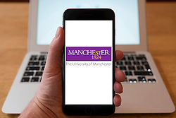 Using iPhone smartphone to display logo of Manchester University.
