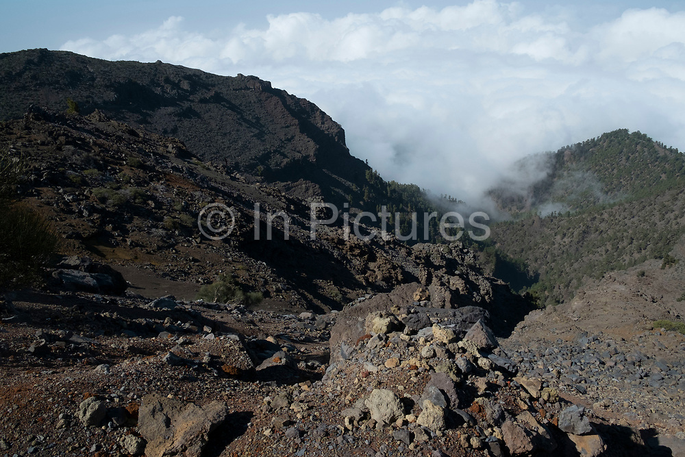View looking south to the Caldera de Taburiente National Park in La Palma, Canary Islands, Spain. La Palma, also San Miguel de La Palma, is the most north-westerly Canary Island in Spain. La Palma has an area of 706km2 making it the fifth largest of the seven main Canary Islands. Caldera de Taburiente National Park Spanish: Parque Nacional de la Caldera de Taburiente is a national park on the island of La Palma, Canary Islands, Spain. It contains the enormous expanse of the Caldera de Taburiente, once believed to be a huge crater, but nowadays known to be a mountain arch with a curious crater shape, which dominates the northern part of the island. It was designated as a national park in 1954. The caldera is about 10km across, and in places the walls tower 2000 m over the caldera floor.