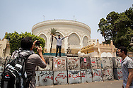 Friends photograph each other on defences built by the military around the presidential palace, in Cairo.