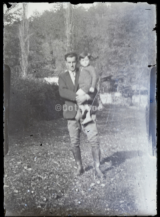 man standing outside holding a little child from a glass negative 1920s