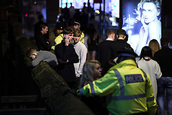 """© Licensed to London News Pictures . 19/12/2015 . Manchester , UK . A man leans over a wall overlooking a canal at Deansgate Locks . Revellers in Manchester enjoy """" Mad Friday """" - also known as """" Black Eye Friday """" - the day on which emergency services in Britain are typically at their busiest , as people head out for parties and drinks to celebrate Christmas . Photo credit : Joel Goodman/LNP"""