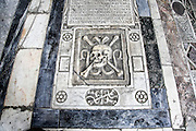 Skull and crossed bones motif on grave slab inside the Camposanto Monumentale cemetery. Pisa, Tuscany, Italy.