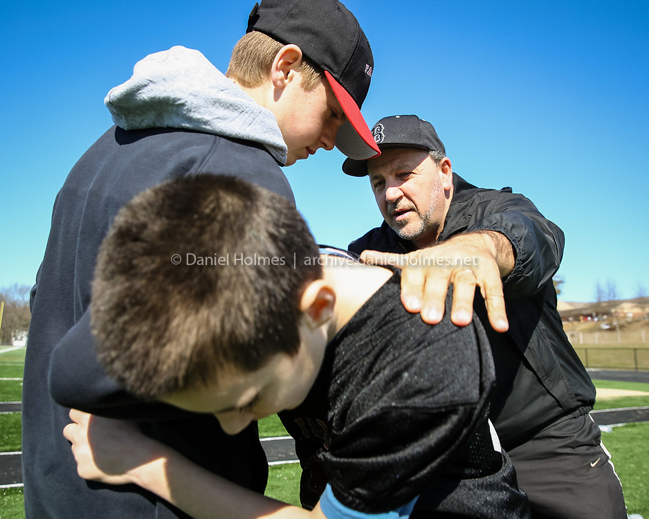 (3/22/16, BELLINGHAM, MA) Bellingham Vice President of youth football Dan Haddad goes over proper tackling technique with Sean Turk, 12, front,  <br /> and Andrew Cochrane, 12, at Bellingham High School on Tuesday. Daily News and Wicked Local Photo/Dan Holmes