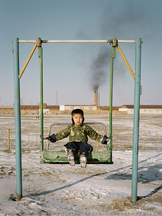 A young boy plays in a russian era playground near Bulgan town, beside a coal factory, Mongolia.<br /> <br /> Travels in the Gobi desert region.