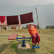 Nuns monk doing outdoor workout gymnastic.<br /> The Sangchhen Dorji Lhuendrup Nunnery is perched on a hilltop overlooking the Punakha valley and Wangduephodrang valley. The nunnery has several hundred women staying and studying the principles of buddhism.