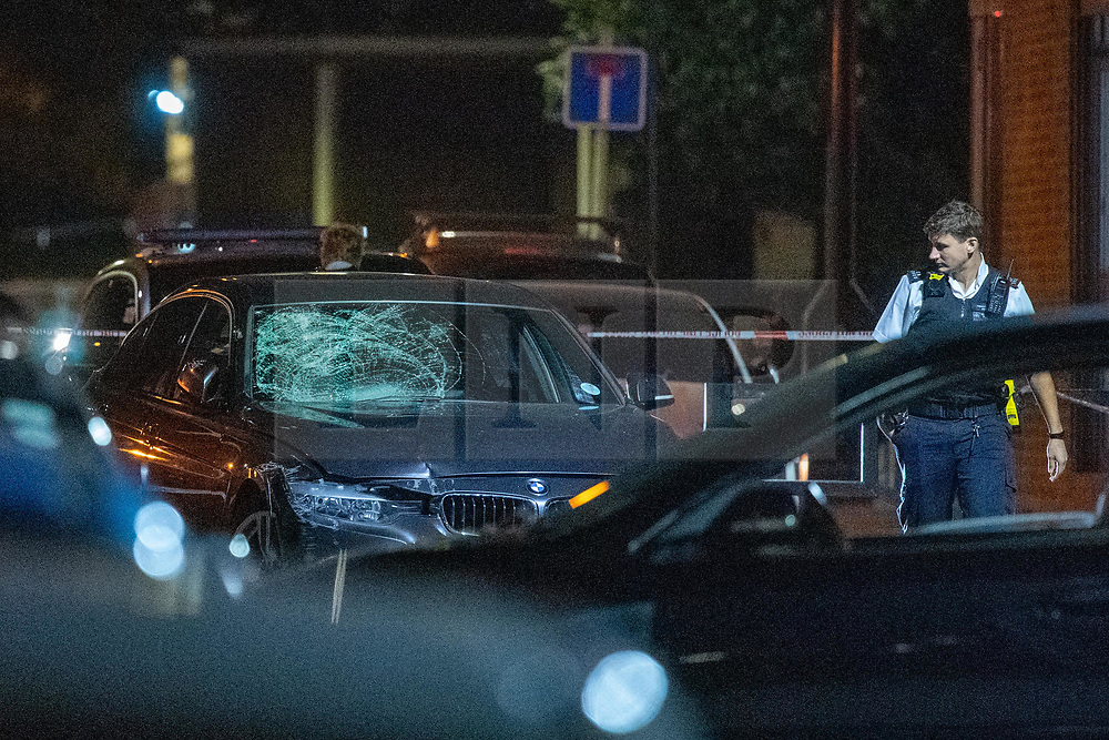 © Licensed to London News Pictures. 20/07/2020. London, UK. A police officer looks at a smashed windscreen on a BMW car inside a police cordon on Scott Street. An investigation has been launched after a person was rammed by a car in Bethnal Green, the person was rammed by the vehicle into a fence. Photo credit: Peter Manning/LNP