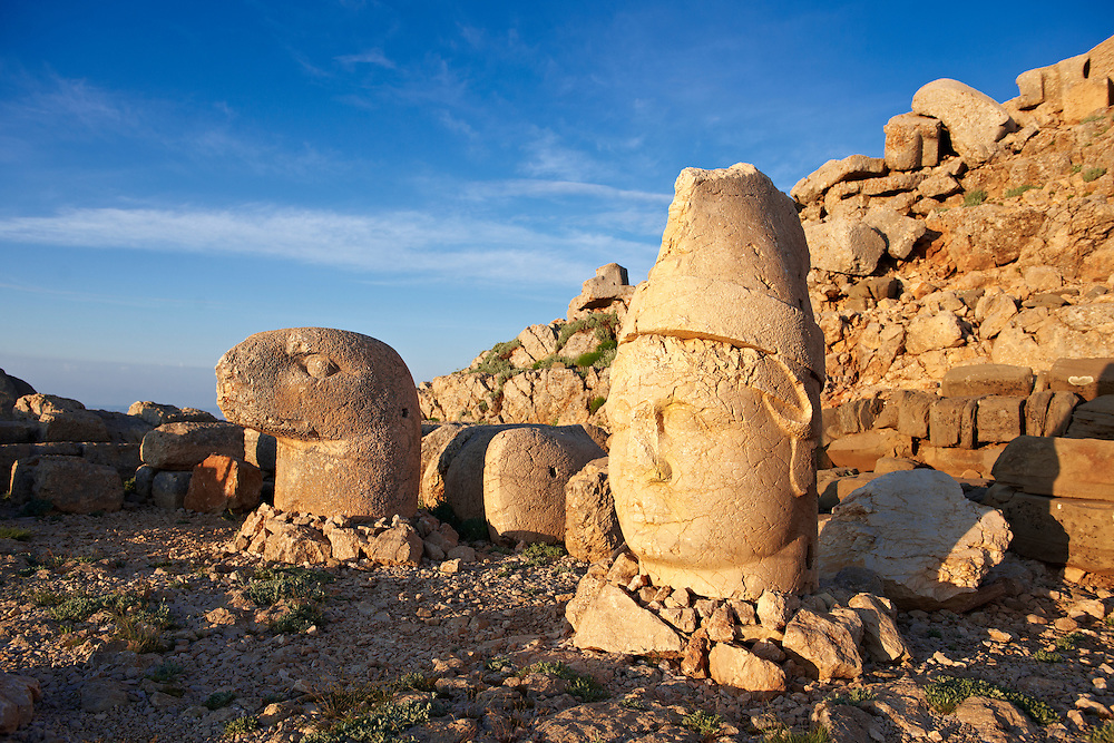 Pictures of the statues of around the tomb of Commagene King Antochus 1 on the top of Mount Nemrut, Turkey. Stock photos & Photo art prints. In 62 BC, King Antiochus I Theos of Commagene built on the mountain top a tomb-sanctuary flanked by huge statues (8–9 m/26–30 ft high) of himself, two lions, two eagles and various Greek, Armenian, and Iranian gods. The photos show the broken statues on the  2,134m (7,001ft)  mountain. .<br /> <br /> If you prefer to buy from our ALAMY PHOTO LIBRARY  Collection visit : https://www.alamy.com/portfolio/paul-williams-funkystock/nemrutdagiancientstatues-turkey.html<br /> <br /> Visit our CLASSICAL WORLD HISTORIC SITES PHOTO COLLECTIONS for more photos to download or buy as wall art prints https://funkystock.photoshelter.com/gallery-collection/Classical-Era-Historic-Sites-Archaeological-Sites-Pictures-Images/C0000g4bSGiDL9rw