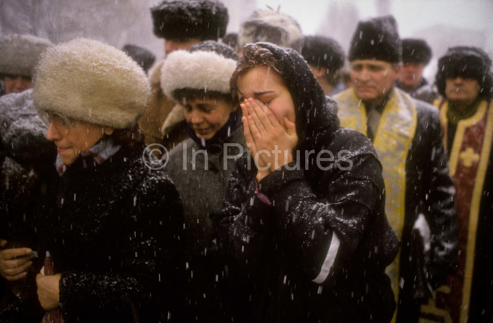 A young women cries at her brother's funeral, one of the numerous heroes of the Romanian revolution that swept the dictator Ceucescu from power over Christmas of 1989, Bucharest, Romania