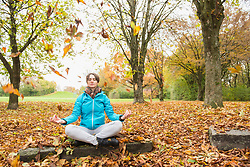 Woman meditating while sitting on a rock in autumn scenery