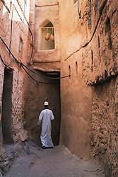 Man walking in alleyway of old traditional village of Misfat al Abryeen in Oman Middle East