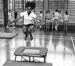 Secondary school girl jumping on trampoline during physical education class,