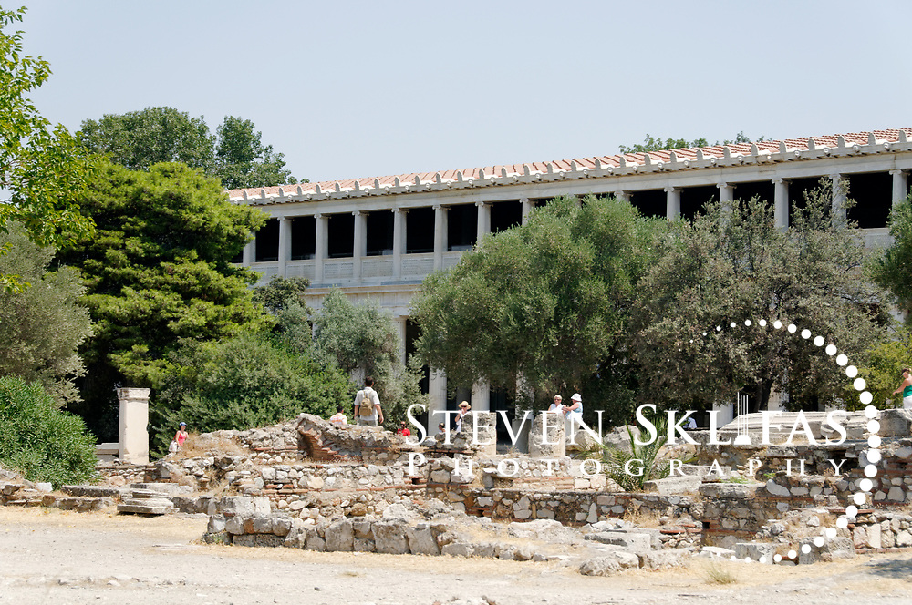 Ancient Agora. Athens. Greece. View of the Stoa of Attalos, a beautifully restored colonnaded building in the Agora. Constructed by King Attalos II of Pergamon between years 159 – 138 BC, it is thought to be used as offices and shops and administrative centre.  It is a two-storeyed building with Doric columns fronting the ground floor exterior with Ionic columns splitting the interior long pillared hall into two aisles. The upper floor is fronted by Ionic columns. The building was faithfully reconstructed in 1953-56 and is used a museum to house finds form the Agora site.