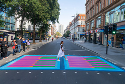 © Licensed to London News Pictures. 16/09/2021. London, UK. A woman walks across a crossing as Bring London Together, a spectacular new public art commission transforming 18 pedestrian crossings with distinctive playful designs is unveiled. The 'Bring London Together' project is designed to draw Londoners and visitors to central London and support the capital's creative, retail and hospitality sectors which have been disproportionately affected by the pandemic. It is the latest instalment of the Mayor's Let's Do London tourism campaign–the largest domestic tourism campaign the capital has ever seen. Photo credit: Ray Tang/LNP