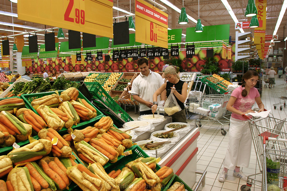 (MODEL RELEASED IMAGE). Scooping out sauerkraut, Marzena Sobczynska leads her husband Hubert and daughter Klaudia through the family's grocery shopping at the Auchan hypermarket. The huge new supermarket, ten minutes' drive from their home, is near a big intersection that serves four or five other bedroom communities.Hungry Planet: What the World Eats (p. 249). The Sobczynscy family of Konstancin-Jeziorna, Poland, is one of the thirty families featured, with a weeks' worth of food, in the book Hungry Planet: What the World Eats.