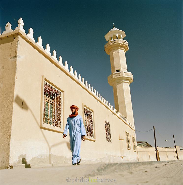 Tuareg Desert Guide walking past a mosque, Libya