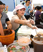 Busy Hmong outdoor restaurant making and serving food. Hmong Sports Festival McMurray Field St Paul Minnesota USA
