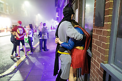 © Licensed to London News Pictures . 27/12/2018. Wigan, UK. Batman and Superwoman hug on King Street . Revellers in Wigan enjoy Boxing Day drinks and clubbing in Wigan Wallgate . In recent years a tradition has been established in which people go out wearing fancy-dress costumes on Boxing Day night . Photo credit: Joel Goodman/LNP
