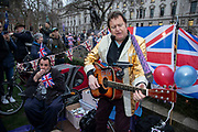 Pro Brexit Leave supporter and Elvis impersonator sings songs as people gather in Westminster on Brexit Day as the UK prepares to leave the European Union on 31st January 2020 in London, England, United Kingdom. At 11pm on Friday 31st January 2020, The UK and N. Ireland will officially leave the EU and go into a state of negotiations as to the future arrangement and trade agreement, while adhering to EU rules until the end of 2020.
