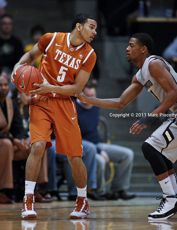 SHOT 2/26/11 3:03:15 PM - Colorado's Cory Higgins (#11) guards Texas' Cory Joseph (#5) during their regular season Big 12 basketball game at the Coors Events Center in Boulder, Co. Colorado upset the fifth ranked Texas 91-89. (Photo by Marc Piscotty / © 2011)