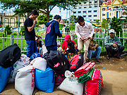 05 JULY 2017 - POIPET, CAMBODIA: Cambodian migrant workers going to Thailand wait for their paperwork before crossing the Thai border. Cambodian migrant workers in Poipet headed for Thailand take a tuk-tuk (three wheeled taxi) to the Thai-Cambodian border. The Thai government proposed new rules for foreign workers recently. The new rules include fines of between 400,000 and 800,00 Thai Baht ($12,000 - $24,000 US) and jail sentences of up to five years for illegal workers and people who hire illegal workers. Hundreds of companies fired their Cambodian and Burmese workers and tens of thousands of workers left Thailand to return to their countries of origin. Employers and human rights activists complained about the severity of the punishment and sudden implementation of the rules. On Tuesday, 4 July, the Thai government suspended the new rules for 180 days and the Cambodian and Myanmar governments urged their citizens to stay in Thailand, but the exodus of workers continued through Wednesday.     PHOTO BY JACK KURTZ
