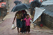 Rohingya refugees shield from the rain in Balukhali, Camp 10, part of the refugee camp sheltering over 800,000 Rohingya refugees, Cox's Bazar, Bangladesh, June 12, 2018. Daily landslides are expected, and agencies have put in place a mass casualty plan, with 200,000 people at risk.