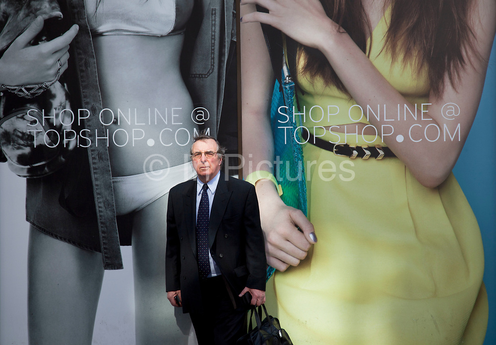 People outside Miss Selfridge retail store dwarfed in scale in front of the large photographic advertising hoardings dipicting slender models. Businessman in contrast to young models in central London on Oxford Street. UK.