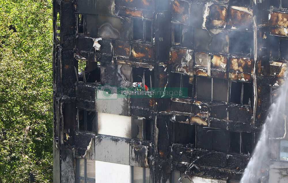 A firefighter inspects the damage after a fire engulfed the 24-storey Grenfell Tower in west London.