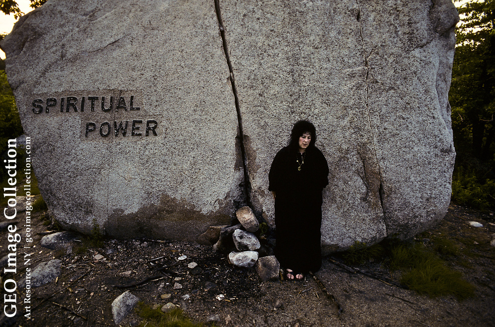 Laurie Cabot, an American Witchcraft High Priestess of Salem, Massachusetts visiting abandoned Dogtown near Gloucester, Massachusetts.  Ms. Cabot was declared the Official Witch of Salem, Massachusetts. She is leaning on one of three dozen Babson Boulders, large boulders carved with inspirational messages during the Great Depression under direction of Roger Babson. This boulder says Spiritual Power and pays homage to Dogtown's association with spirits, witches, and witchcraft. Dogtown was a settlement home to women who were persecuted as witches in early Massachusetts.
