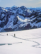 Hikers descend snow on Sahale Glacier on Sahale Arm, in North Cascades National Park, Washington, USA. Rising in the upper center is Mount Formidable. On the horizon are Glacier Peak (10,541 ft, left) and Mount Rainier (upper right). Immediately across the valley of North Fork of Cascade River is Cache Col Glacier on the east slope of Mix-up Peak. October 1, 1982.