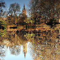 University of Glasgow bathed in autumn sunshine and reflected in Kelvingrove park pond.