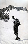 man with rock climbing gear walking in the mountains Alps France 1935