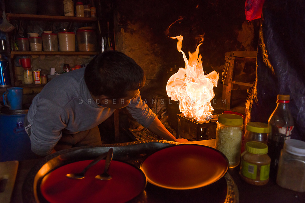 A man lights a stove in a lodge in Thare, Nepal Himalaya. Photo © robertvansluis.com