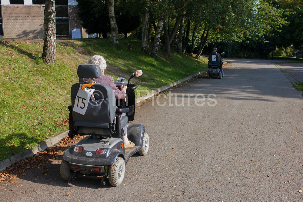 A couple riding on rented mobility scooters in the grounds of the Yorkshire Sculpture Park. With identifying codes on the rear of each vehicle, the couple make their way to another art installation and although on an internal roadway, keeping to the left, as if on a European road. In one mirror of the nearest scooter, we see the occupant's face, an elderly lady with white hair and glasses. In the distance is her husband who has raced ahead into the shadows.