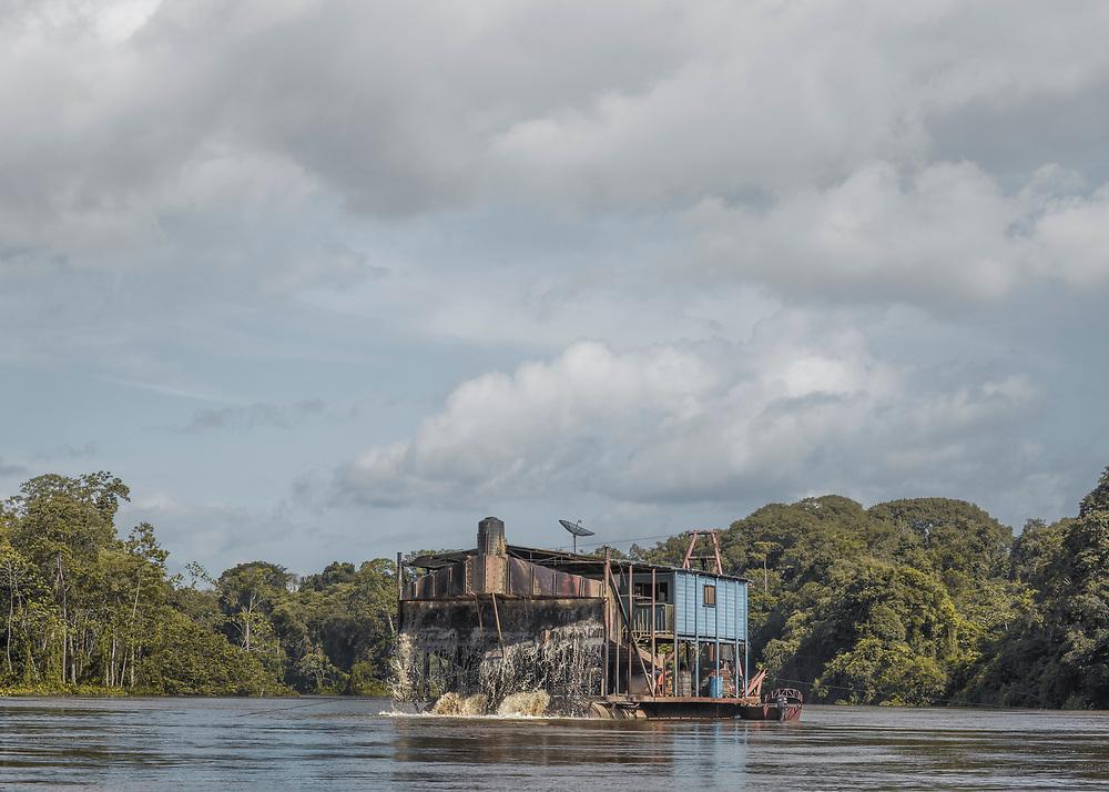 Grand-Santi, Maroni, 2015.<br /> <br /> Barge d'orpaillage face à la commune de Grand-Santi. Depuis les efforts entrepris par le gouvernement français pour juguler l'orpaillage clandestin dans l'Ouest guyanais, les barges qui avaient pratiquement disparues réapparaissent sur le Maroni, fleuve frontalier du Suriname. Les pompes de cette embarcation aspirent le fond du fleuve à la recherche d'or alluvionnaire. L'embarcation possède trois chambres climatisées, une cuisinière Surinamaise et quatre ouvriers brésiliens assurent le bon fonctionnement du travail. La mouvance des eaux et la mobilité du procédé rendent difficilement contrôlable ce travail de l'or à la frontière de la légalité. <br /> <br /> La convention de Paris signée entre la France et les Pays-Bas le 30 septembre 1915 stipule que « la frontière entre la France et le Suriname est précisément délimitée entre l'île Portal (proche de Saint-Laurent du Maroni) et l'île Stoelman (plus haut sur le Maroni) par la ligne médiane du fleuve Maroni. Cette convention de 1915 établit également « un régime de liberté de navigation sur cette portion du fleuve. Les contrôles de police aux fins de prévention ou de répression d'infractions pénales y sont licites dans la mesure où ils n'entravent pas sans justification cette liberté ». Dans les faits, sur les eaux mouvantes du Maroni, il n'existe pas de délimitation conventionnelle de l'emplacement exact de la frontière dans le lit du fleuve qui ne soit contestable.<br /> <br /> Strictement interdites en France mais tolérées de l'autre côté de la frontière, une trentaine de barges sont recensées le long du fleuve en décembre 2014.