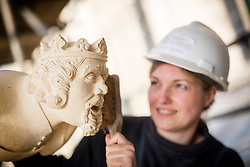 © Licensed to London News Pictures. 27/09/2017. York UK. Stone Mason Victoria Darley inspects the first collection of new grotesques to be carved for York Minster's 11 year project to conserve its South Quire Aisle have been installed today. The four carvings have been based on the Judgement of Solomon & include King Solomon, two women- one carrying a baby & a dragon holding a goose between it's teeth. The grotesques are being returned to a newly restored pinnacle, to replace four weathered carvings which are believed to date from the 1700s. Although badly eroded, the cathedral's stonemasons could make out two women - one holding a bundle – a male figure and evidence of a winged beast with a bird between its teeth. Work on the South Quire Aisle, which dates from the 14th century, began at the start of 2016 and will involve an £11m investment over the next decade to repair and replace stone and glass in 15 window bays.Photo credit: Andrew McCaren/LNP