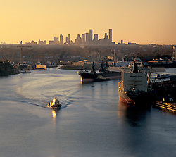 Tugboat and shipping vessels in the ship channel at the Port of Houston with the downtown Houston skyline on the horizon at sunrise.