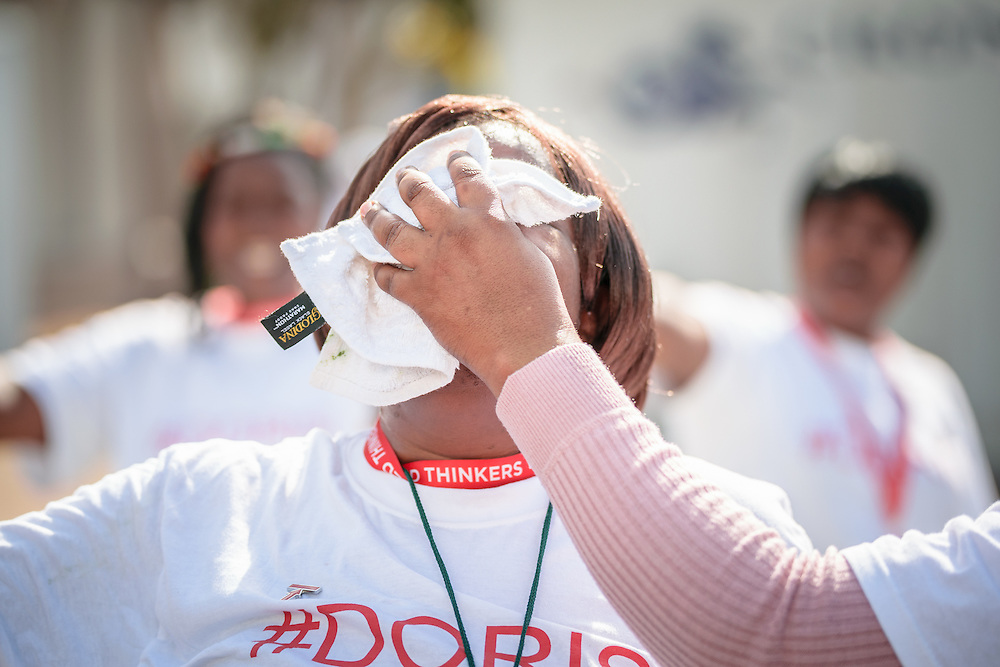 """Protestors demand better treatment for caregivers and health workers at the 2016 International AIDS Conference in Durban, South Africa, saying """"When health workers suffer, society suffers"""". As part of the demonstration, protestors perform stunt where a person gets her tears forcefully wiped from her face using a white cloth."""