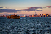 A Staten Island Ferry sails across the Upper Bay at sunset away from Lower Manhattan, also know as Downtown Manhattan which is the financial district and centre for business, culture and government in the city of New York, United States of America.
