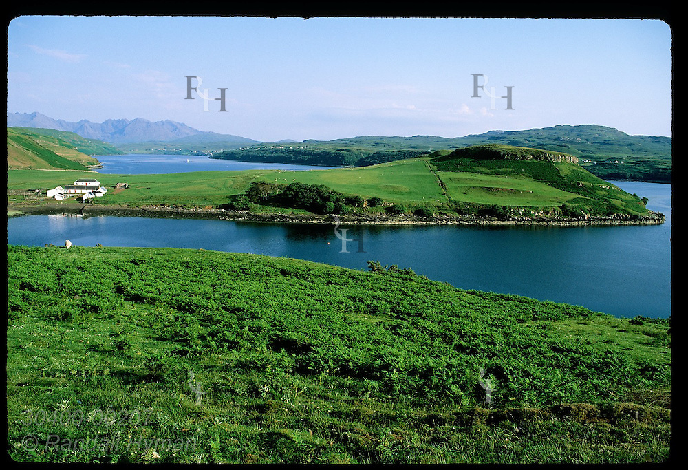 Grassy spit of farmland juts out into Loch Harport on a sunny July evening; Isle of Skye. Scotland