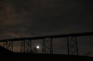 Salisbury Mills, New York  - The moon shines through clouds under the Moodna Viaduct railroad trestle on Nov. 27, 2011.