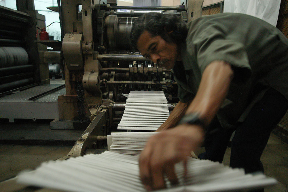 Collecting newspapers off the folding machine at the Co-Latino newspaper, San Salvador