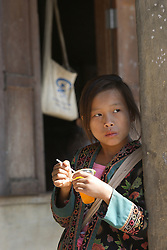 Vamour, dressed in her ethnic clothes drinks an orange juice during the morning break..<br /> Viengpathana primary School,   Pha Oudom District, Bokeo Province, Lao PDR