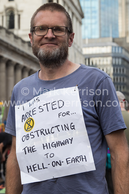 An Extinction Rebellion climate activist protests in front of the Bank of England in the City of London on the eleventh day of Impossible Rebellion protests on 2nd September 2021 in London, United Kingdom. Over 50 activists wore signs indicating that they were breaking restrictive bail conditions by entering the City of London. Extinction Rebellion are calling on the UK government to cease all new fossil fuel investment with immediate effect.