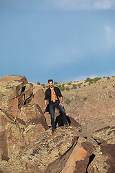 cowboy with open shirt on a rock formation
