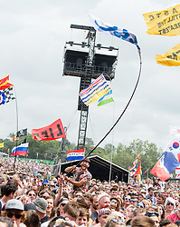 © Licensed to London News Pictures. 26/06/2015. Pilton, UK.  Festival goers wave flags and have flag-battles as they watch James Bay at Glastonbury Festival 2015 on the Pyramid Stage on Friday Day 3 of the festival.  This years headline acts include Kanye West, The Who and Florence and the Machine, the latter being upgraded in the bill to replace original headline act Foo Fighters.   Photo credit: Richard Isaac/LNP