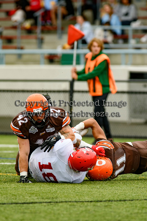 CHILLIWACK, BC - SEPTEMBER 11: Roy Outh #18 of Westshore Rebels is tackled by Peyton Ryder #42 and Donovin Small #11 of Okanagan Sun during third quarter at Exhibition Stadium in Chilliwack, BC, Canada. (Photo by Marissa Baecker/Shoot the Breeze)