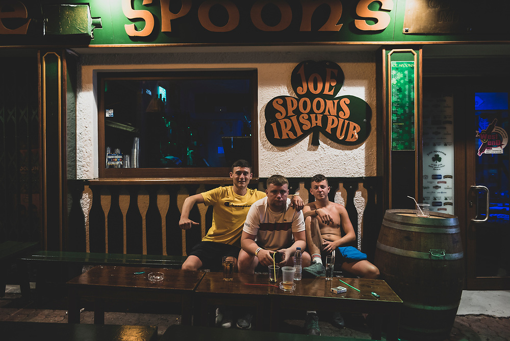 San Antonio, Ibiza, Spain - July 29, 2018: James Connolly, Simon Sackey, and Patrick Kelly sit outside Joe Spoons Irish Pub on Carrer de Santa Agnès in San Antonio, Ibiza.